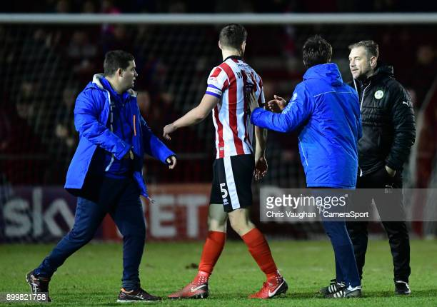 Lincoln City manager Danny Cowley second in from right moves Lincoln City's Luke Waterfall away from Forest Green Rovers' assistant manager Scott...