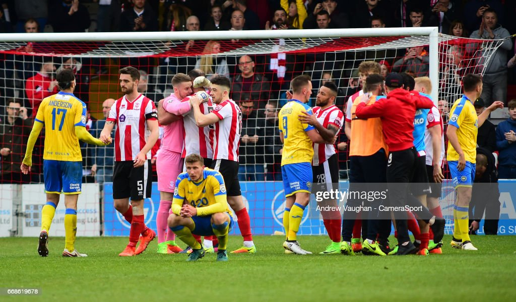 Lincoln City players celebrate the victory at the final whistle of the Vanarama National League match between Lincoln City and Torquay United at Sincil Bank Stadium on April 14, 2017 in Lincoln, England.