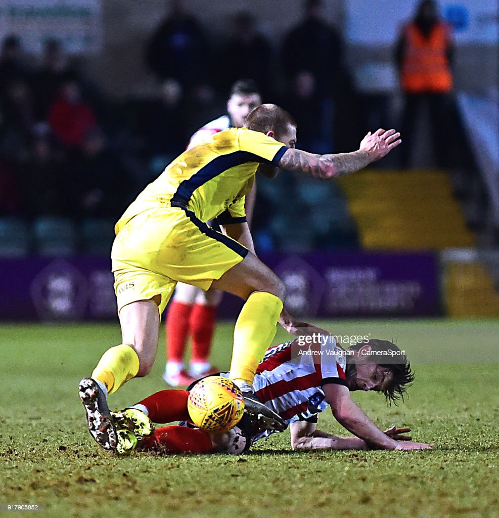 Lincoln City's Alex Woodyard vies for possession with Cheltenham Town's Harry Pell during the Sky Bet League Two match between Lincoln City and Cheltenham Town at Sincil Bank Stadium on February 13, 2018 in Lincoln, England.
