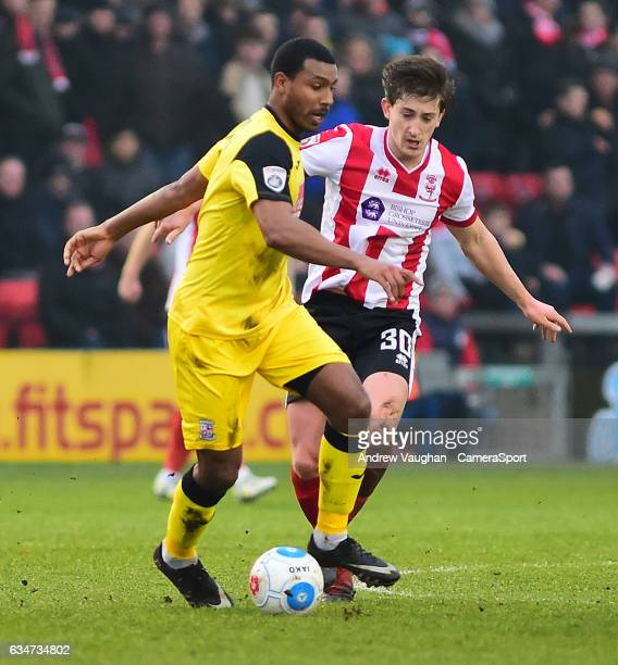Lincoln City's Alex Woodyard vies for possession with Woking's Terell Thomas during the Vanarama National League match between Lincoln City and...