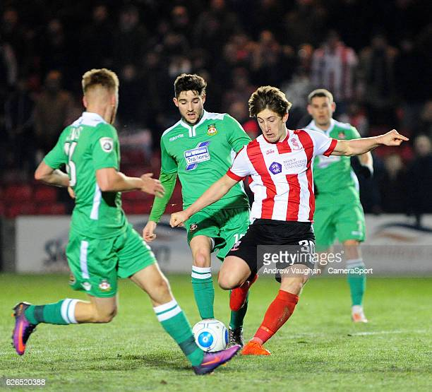 Lincoln City's Alex Woodyard vies for possession with Wrexham's Jordan Evans and Rob Evans during the Vanarama National League match between Lincoln...