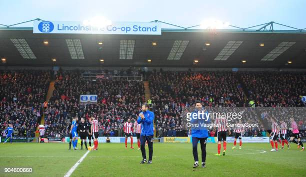 Lincoln City's assistant manager Nicky Cowley left and Lincoln City manager Danny Cowley applaud the fans prior to the Sky Bet League Two match...