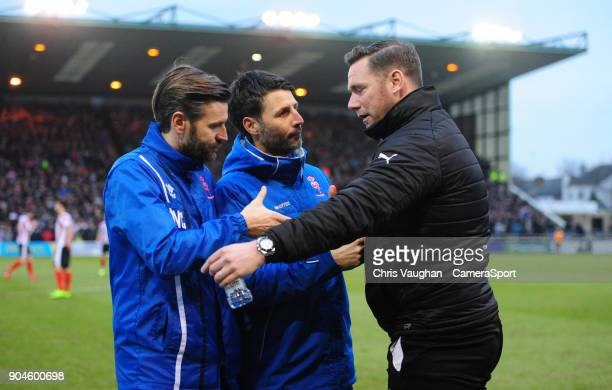 Lincoln City's assistant manager Nicky Cowley left and Lincoln City manager Danny Cowley centre shake hands with Notts County manager Kevin Nolan...