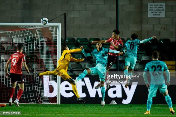 Lincoln City's Dutch defender Lewis Montsma jumps to head the ball past Liverpool's Brazilian midfielder Fabinho and Liverpool's Spanish goalkeeper...