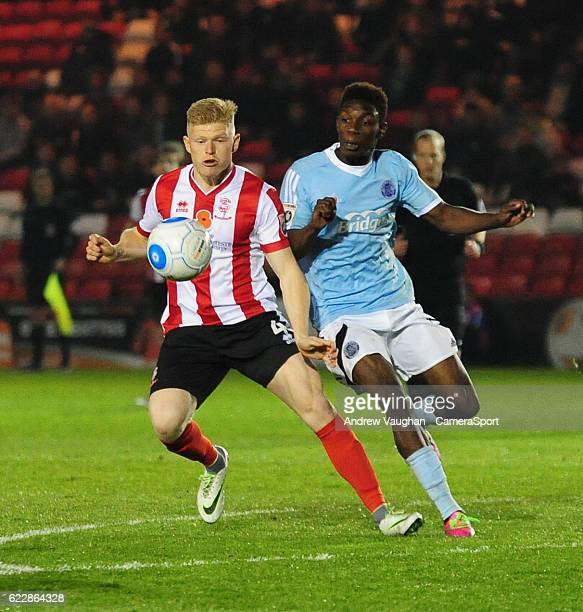 Lincoln Citys Elliott Whitehouse vies for possession with Aldershot Town's Bernard Mensah during the Vanarama National League match between Lincoln...