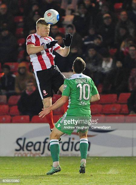 Lincoln Citys Elliott Whitehouse vies for possession with Wrexham's John Rooney during the Vanarama National League match between Lincoln City and...