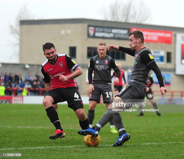 Lincoln City's Harry Toffolo crosses under pressure from Morecambe's Alex Kenyon during the Sky Bet League Two match between Morecambe and Lincoln...