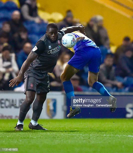 Lincoln City's John Akinde battles with Mansfield Town's Ryan Sweeney during the Sky Bet League Two match between Mansfield Town and Lincoln City at...