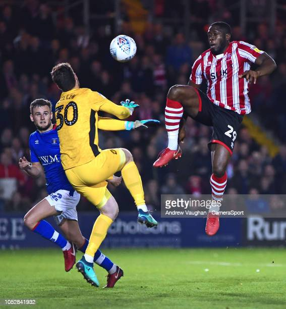 Lincoln City's John Akinde is denied a goal scoring opportunity by Carlisle United's Adam Collin during the Sky Bet League Two match between Lincoln...