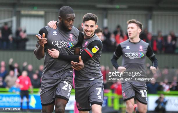 Lincoln City's John Akinde left celebrates scoring his side's second goal with teammate Tom Pett during the Sky Bet League Two match between Forest...