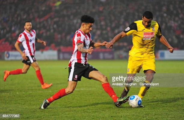 Lincoln City's Josh Ginnelly vies for possession with Woking's Kieran Murtagh during the Vanarama National League match between Lincoln City and...
