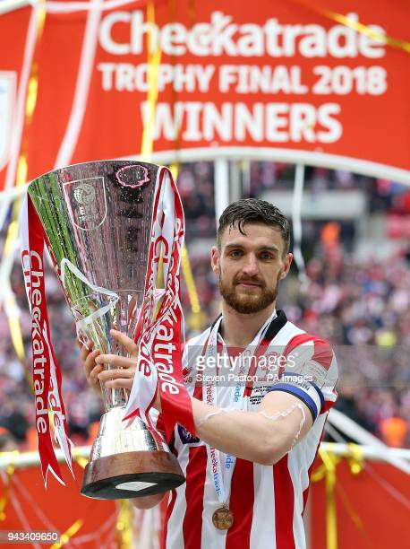 Lincoln City's Luke Waterfall celebrates with the trophy after winning the Checkatrade Trophy final at Wembley Stadium London