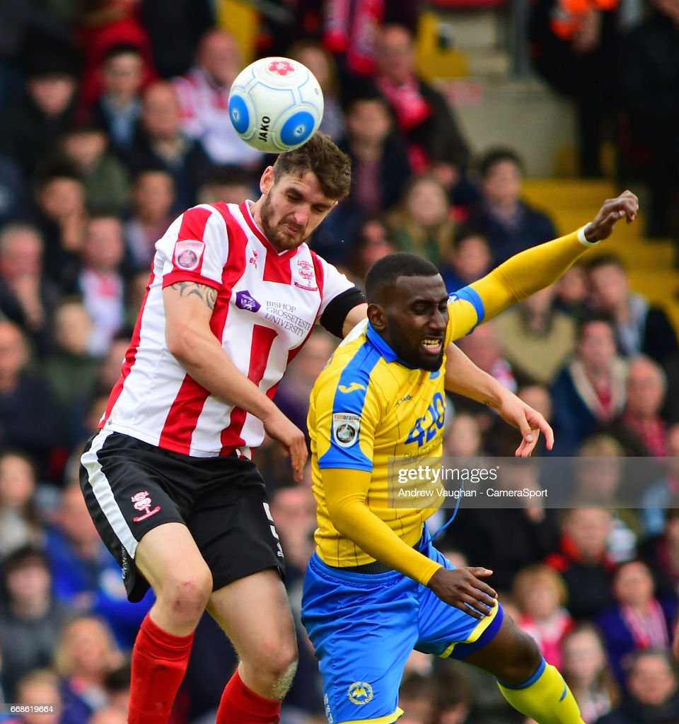 Lincoln City's Luke Waterfall vies for possession with Torquay United's Lathaniel Rowe-Turner during the Vanarama National League match between Lincoln City and Torquay United at Sincil Bank Stadium on April 14, 2017 in Lincoln, England.