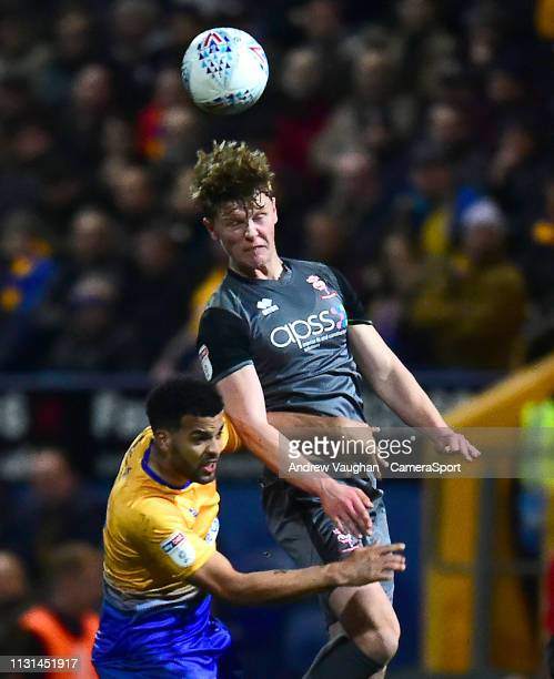 Lincoln City's Mark O'Hara battles with Mansfield Town's Jacob Mellis during the Sky Bet League Two match between Mansfield Town and Lincoln City at...