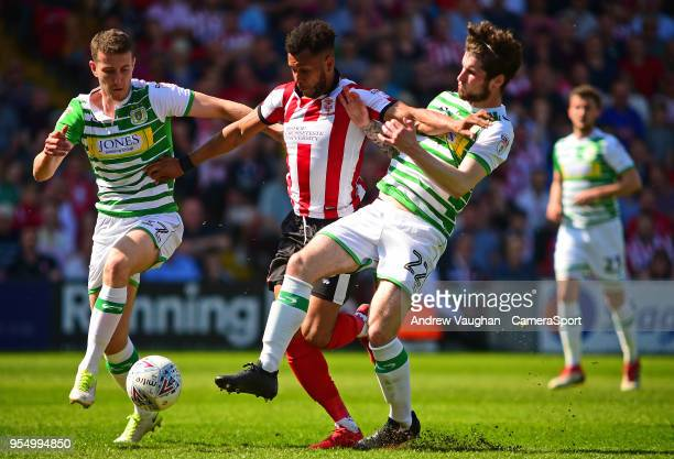 Lincoln City's Matt Green gets between Yeovil Town's Shaun Donnellan left and Corey Whelan right during the Sky Bet League Two match between Lincoln...