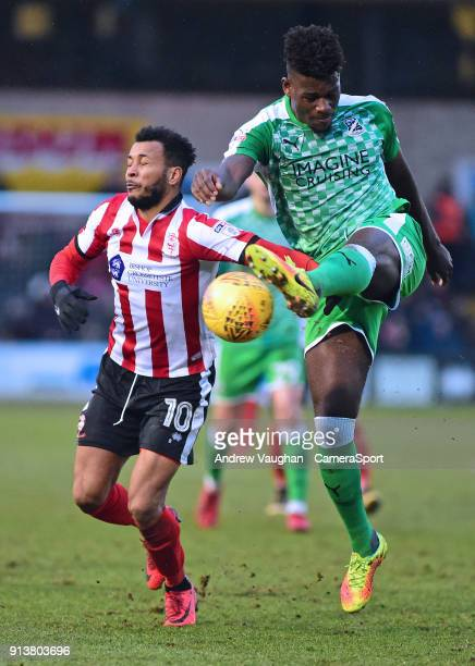 Lincoln City's Matt Green vies for possession with Swindon Town's Rollin Menayese during the Sky Bet League Two match between Lincoln City and...
