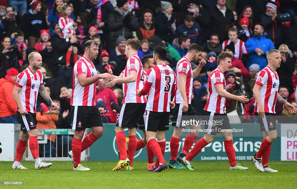 Lincoln City's Matt Rhead celebrates scoring the opening goal with team mates during the Vanarama National League match between Lincoln City and Woking at Sincil Bank Stadium on February 11, 2017 in Lincoln, England.