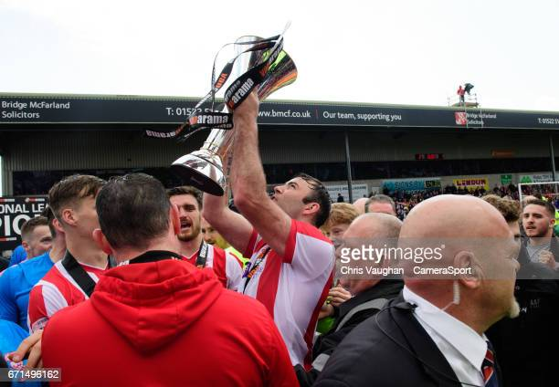 Lincoln City's Matt Rhead celebrates with the Vanarama National League trophy after the Vanarama National League match between Lincoln City and...