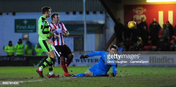 Lincoln City's Matt Rhead chips the ball over Forest Green Rovers' Bradley Collins to score his sides second goal during the Sky Bet League Two match...