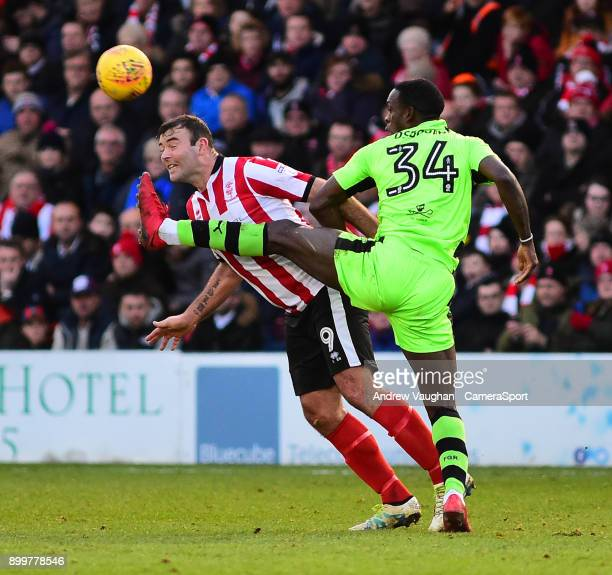 Lincoln City's Matt Rhead vies for possession with Forest Green Rovers' Isaiah Osbourne during the Sky Bet League Two match between Lincoln City and...
