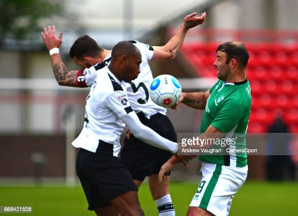 Lincoln City's Matt Rhead vies for possession with Gateshead's Liam Hogan and Emanuel Smith during the Vanarama National League match between...