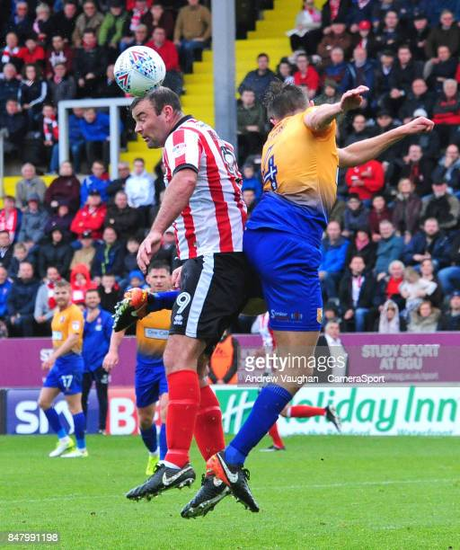 Lincoln City's Matt Rhead vies for possession with Mansfield Town's Paul Digby during the Sky Bet League Two match between Lincoln City and Mansfield...