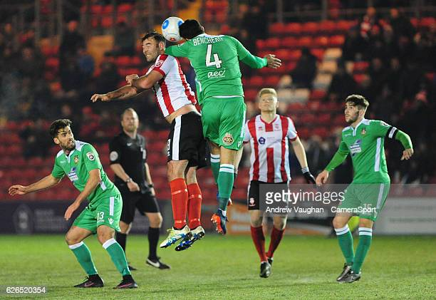 Lincoln City's Matt Rhead vies for possession with Wrexham's Hamza Bencherif during the Vanarama National League match between Lincoln City and...