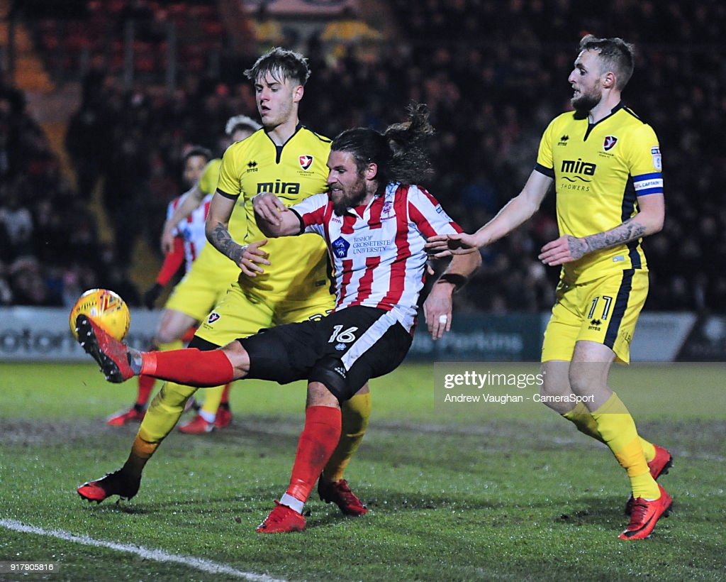 Lincoln City's Michael Bostwick vies for possession with Cheltenham Town's Joe Rodon, left and Cheltenham Town's Carl Winchester during the Sky Bet League Two match between Lincoln City and Cheltenham Town at Sincil Bank Stadium on February 13, 2018 in Lincoln, England.