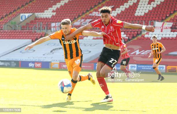 Lincoln City's Morgan Rogers holds off the challenge from Hull City's Regan Slater during the Sky Bet League One match between Lincoln City and Hull...