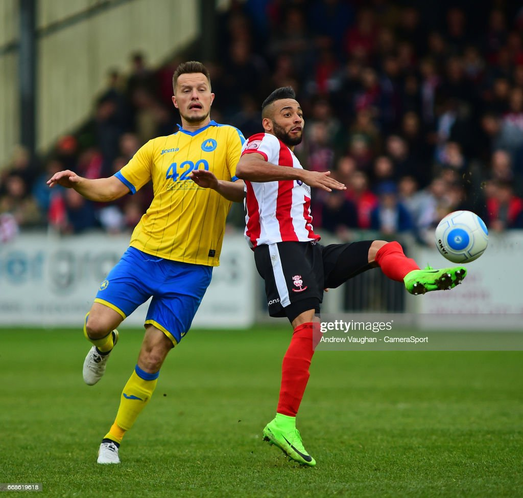 Lincoln City's Nathan Arnold vies for possession with Torquay United's Shaun Harrad during the Vanarama National League match between Lincoln City and Torquay United at Sincil Bank Stadium on April 14, 2017 in Lincoln, England.