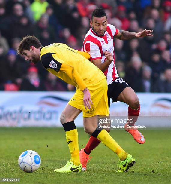 Lincoln City's Nathan Arnold vies for possession with Woking's Joe Jones during the Vanarama National League match between Lincoln City and Woking at...