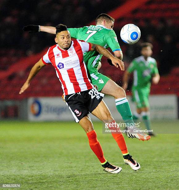 Lincoln City's Nathan Arnold vies for possession with Wrexham's Anthony Barry during the Vanarama National League match between Lincoln City and...