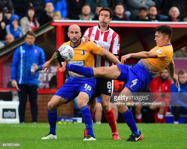 Lincoln City's Ollie Palmer vies for possession with Mansfield Town's David Mirfin and Paul Digby during the Sky Bet League Two match between Lincoln...
