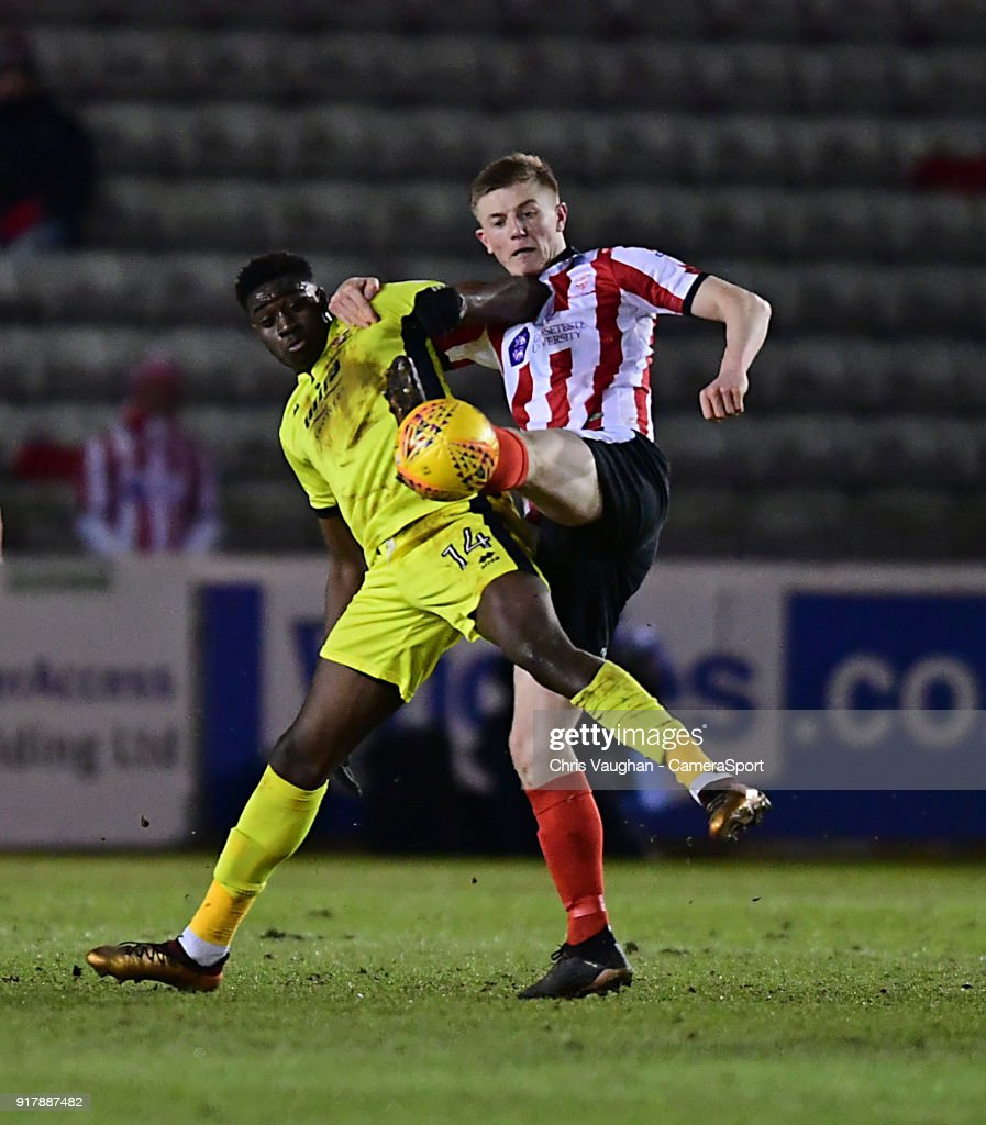 Lincoln City's Scott Wharton vies for possession with Cheltenham Town's Elijah Adebayo during the Sky Bet League Two match between Lincoln City and Cheltenham Town at Sincil Bank Stadium on February 13, 2018 in Lincoln, England.