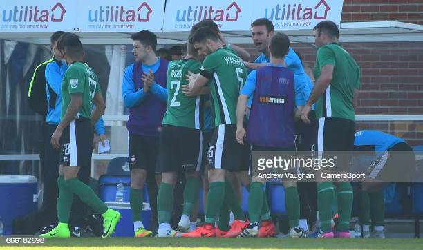 Lincoln City's Sean Raggett celebrates scoring the opening goal with the bench during the Vanarama National League match between Eastleigh and...