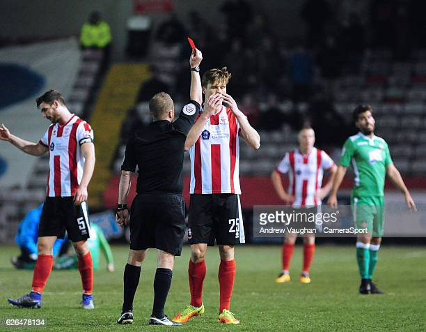 Lincoln City's Sean Raggett is shown a red card by referee David Rock during the Vanarama National League match between Lincoln City and Wrexham at...