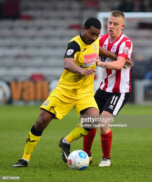 Lincoln City's Terry Hawkridge vies for possession with Woking's Kieran Murtagh during the Vanarama National League match between Lincoln City and...