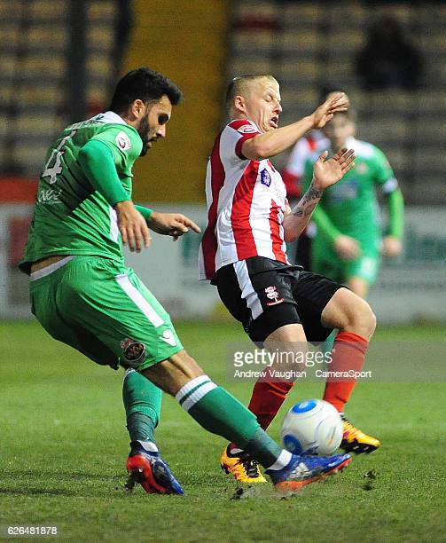 Lincoln City's Terry Hawkridge vies for possession with Wrexham's Hamza Bencherif during the Vanarama National League match between Lincoln City and...