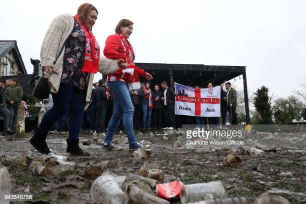 Lincoln fans hold onto each others hands as they make their way through mud and plastic cups ahead the Checkatrade Trophy Final between Lincoln City...
