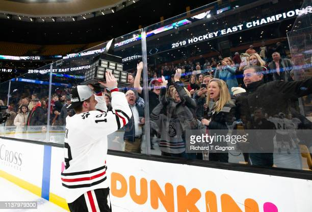 Lincoln Griffin of the Northeastern Huskies celebrates with the Lamoriello Trophy after NCAA hockey against the Boston College Eagles in the Hockey...