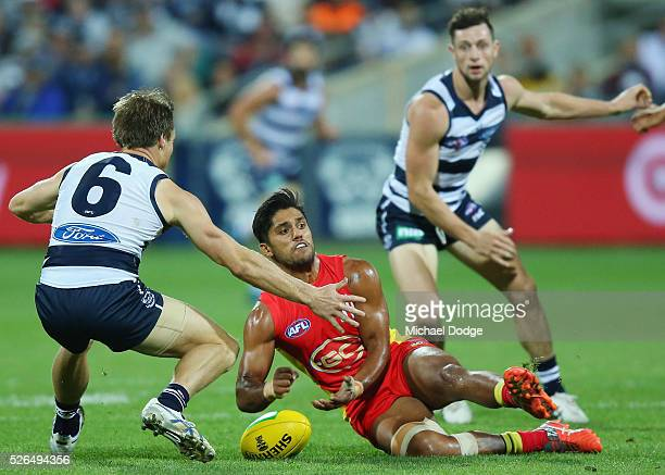 Lincoln McCarthy of the Cats tackles Aaron Hall of the Suns during the round six AFL match between the Geelong Cats and the Gold Coast Suns at...