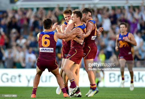 Lincoln McCarthy of the Lions celebrates with his team mates after kicking the match winning goal during the round 22 AFL match between the Brisbane...