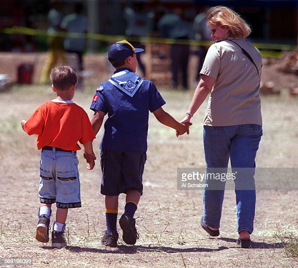 Linda Adintori, of Laguna Niguel, holds the hand of her son, Evan Adintori of Cub Scout Pack 771 of Laguna Niguel, and his friend, Stephen Lane left,...