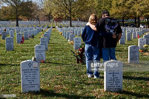 Linda and Gene Lamie of Georgia stand before the grave of their son Sgt Gene L Lamie on Veteran's Day at Arlington National Cemetery on November 11...