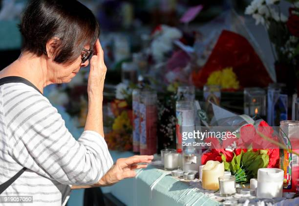 Linda Barrio crosses herself as she prays Friday morning Feb 16 2018 at a memorial at Pine Trails Park in Parkland for the 17 people killed Wednesday...