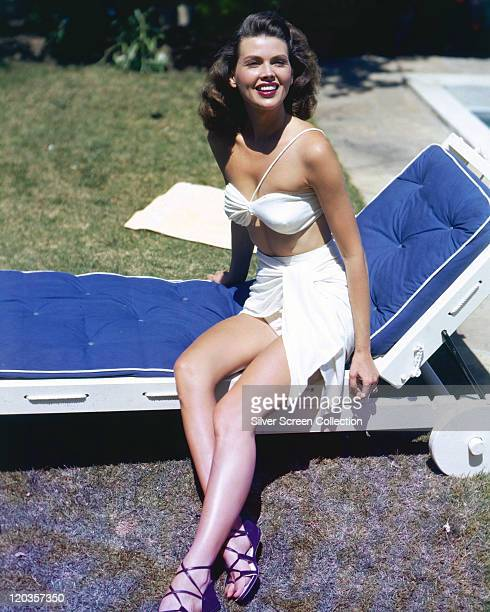 Linda Christian Mexican actress wearing a white bikinj and a short white sarong while sitting on a blue sunlounger circa 1955