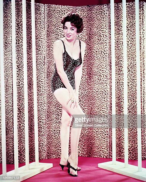 Linda Cristal Argentine actress wearing a leopard print swimsuit while posing in front of a leopard print curtain in a studio portrait 1958
