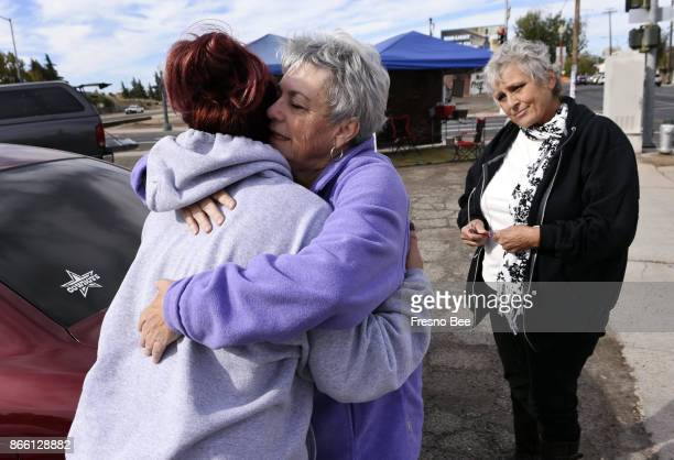 Linda Crowder center hugs Chasity Barajas left who stopped by to receive a prayer from Crowder and Virginia La Salle right at a pair of canopies set...