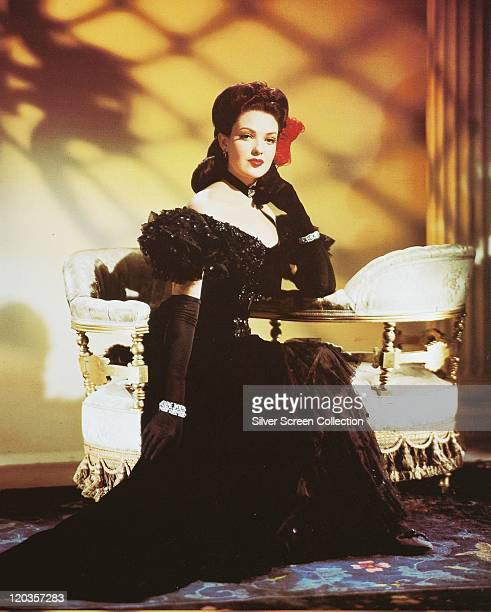 Linda Darnell US actress wearing a black dress with long black gloves and a black choker with a red flower in her hair sitting on a sofa in a studio...