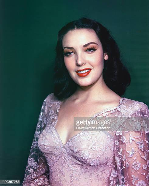 Linda Darnell US actress wearing a pink lace top while smiling in a studio portrait against a green background circa 1950